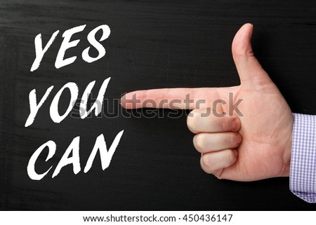 Hand and finger pointing at the words Yes You Can in white text on a blackboard as a reminder to believe in yourself and your abilities
