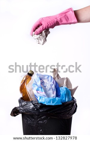 Hand and full trash bin, isolated on white - stock photo
