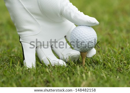 Hand and golf ball on green grass outdoor close up  - stock photo