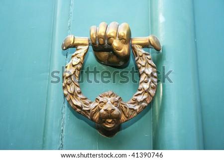 hand and lion head door knocker. - stock photo