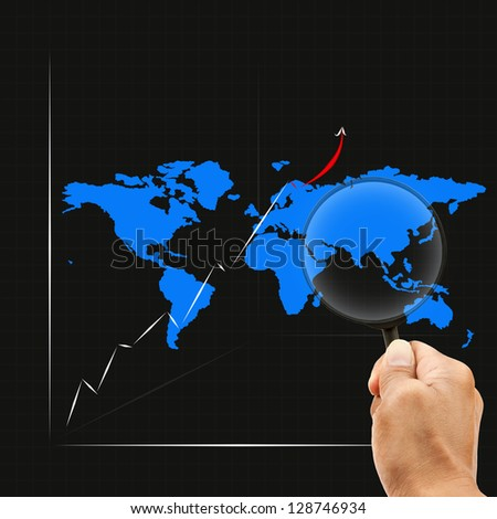 hand and magnifying lens watching on graph map around asia - stock photo