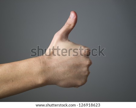 Hand and ok symbol isolated on dark background.