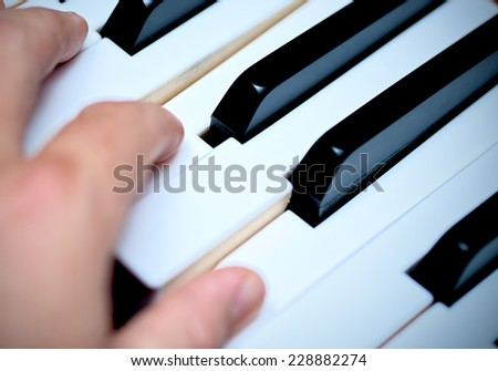 Hand and Piano Keys, Playing Piano - stock photo