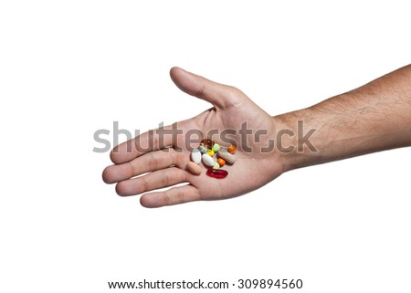 Hand and pills.Man's hand bottomed in riding a white isolated background, IN ITS MANY TABLETS bottomed different colors and shapes. in male hand Many different tablets.HAND closeup with pills  - stock photo