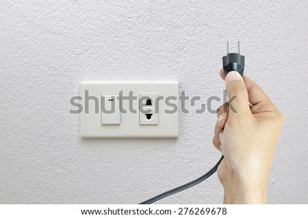 Hand and Plug  Electricity Socket on clean cement plaster wall background , concept electric - stock photo