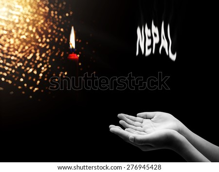 Hand and red candle , Peace to Nepal  - stock photo