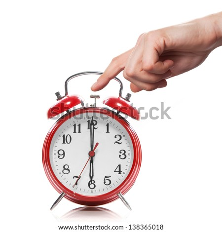 hand and red old style alarm clock isolated on white - stock photo