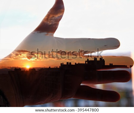 Hand and sunset in the city. Double exposure taken with the camera - stock photo
