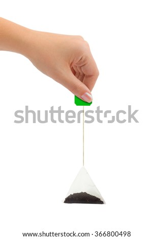 Hand and tea bag isolated on white background - stock photo