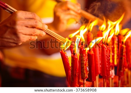Hand and the fire candle and the burning stick , burning candle and burning incense. - stock photo