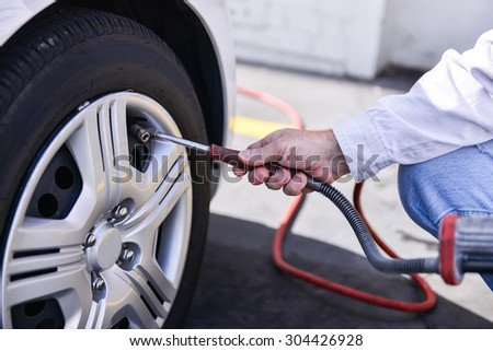 hand and vehicle wheel add air pressure - stock photo