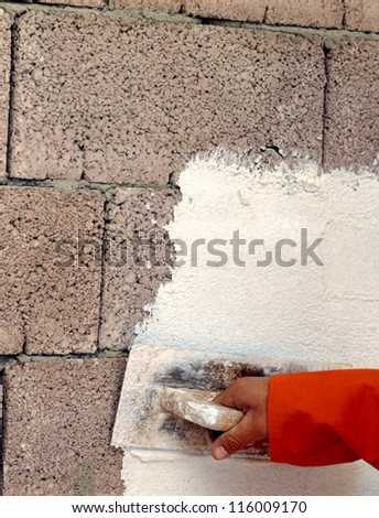 Hand applying plaster to a wall with a trowel