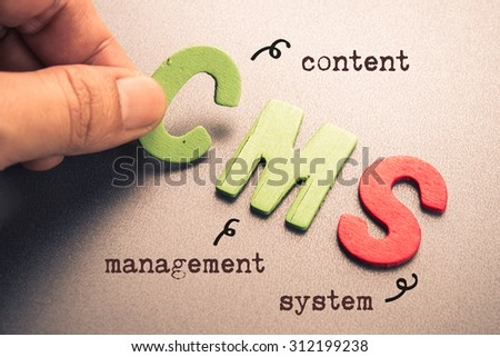 Hand arrange wood letters as CMS (Content Management System) - stock photo