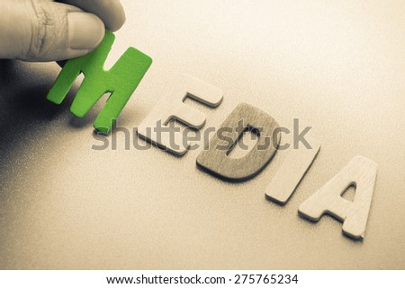 Hand arrange wood letters as Media word - stock photo