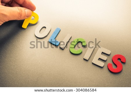 Hand arrange wood letters as Policies word - stock photo