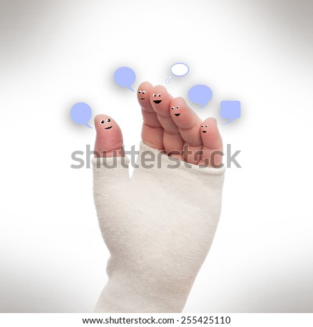 Hand bandaged with smileys and lettering boxes - stock photo