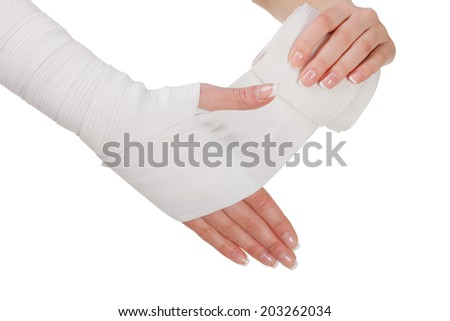 Hand bandaging by elastic bandage. Close up. It is isolated on a white background.
