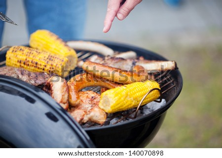 Hand Barbecuing Meat And Corn - stock photo