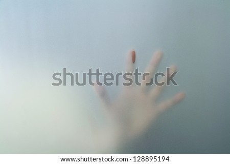 hand behind frosted glass - stock photo