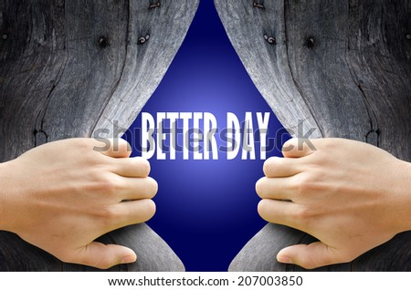 """Hand breaking a wooden wall found the word """"BETTER DAY"""" on the magic blue background. - stock photo"""