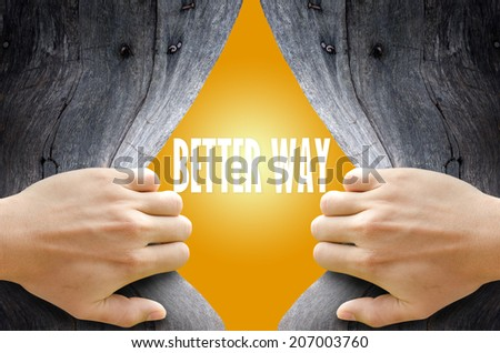 """Hand breaking a wooden wall found the word """"BETTER WAY"""" on the bright yellow background. - stock photo"""