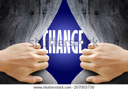 "Hand breaking a wooden wall found the word ""CHANGE"" on the magic blue background. - stock photo"