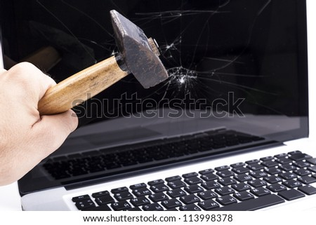 Hand breaking laptop screen with a hammer - stock photo