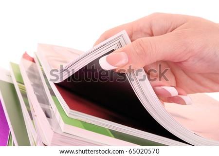 hand browsing through stack of magazines - stock photo