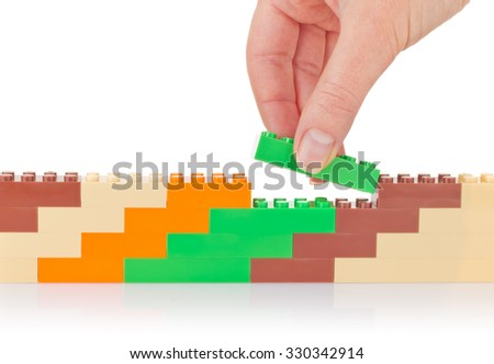 Hand build wall of colour toy block. Isolated on white background