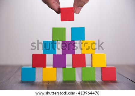 Hand building Colorful stack of wood cube blocks - stock photo