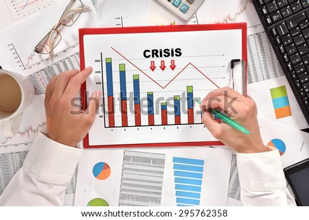 hand businessman drawing crisis chart in clipboard - stock photo