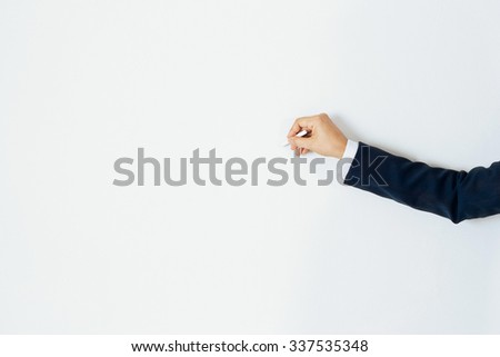 Hand businessman writing with copy space for text on pastel color wall background - stock photo