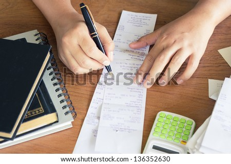 Hand calculate bills on the table - stock photo