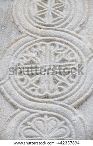Hand-carved patterns in white natural stone as part of the facade or pillars. - stock photo