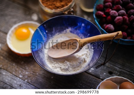 hand carved wooden spoon and cooking a cherry pie - stock photo