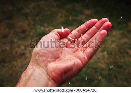 Hand catching drops in dry landscape, rare water. - stock photo