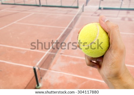 hand catching tennis ball with tennis stadium background  - stock photo
