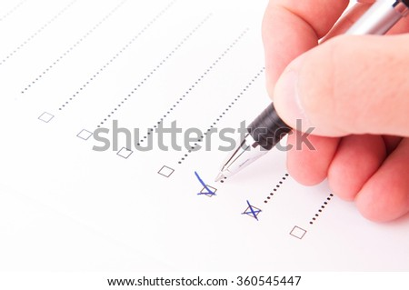 Hand checking a box with a yes with a pen