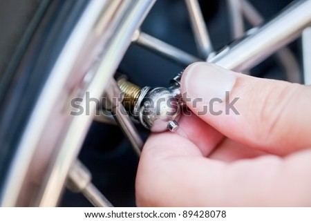 Hand checking tire pressure - stock photo