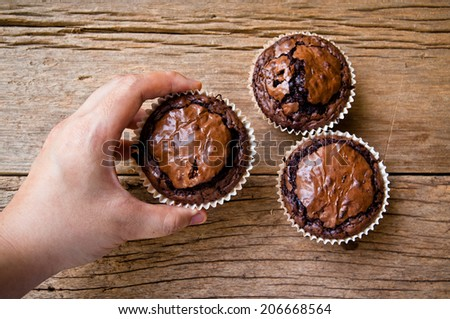 Hand, Chocolate muffins with crispy top on Wood Table Background, Rustic Still Life Style / Concept and Idea of Sweet Food Bakery Dessert Time, To Eat with Coffee or Hot Drink in Morning or Tea Time. - stock photo