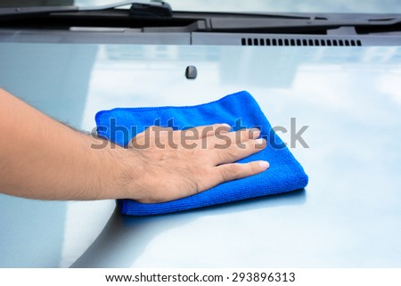 Hand cleaning car bonnet with microfiber cloth