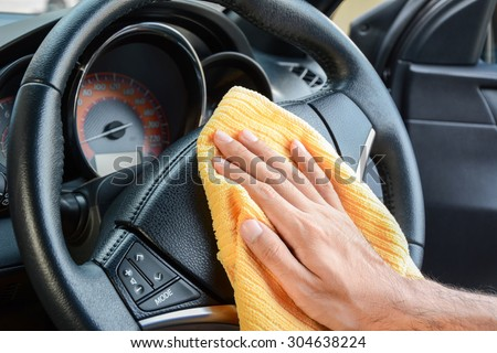Hand cleaning car steering wheel with microfiber cloth, auto detailing (valeting) concept - stock photo