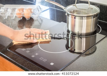 Hand cleaning cooker at home kitchen - stock photo