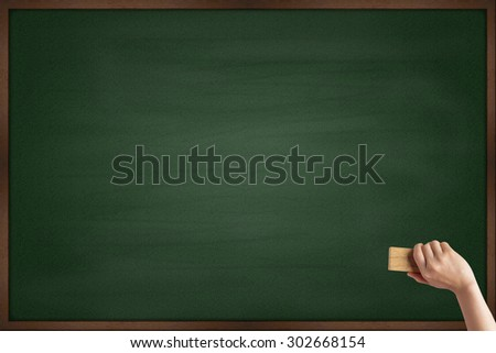 Hand cleaning the chalkboard - stock photo
