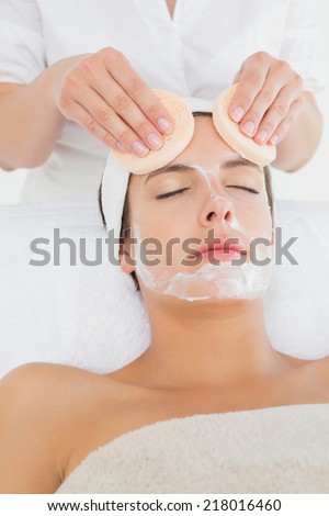 Hand cleaning womans face with cotton swabs at spa center - stock photo