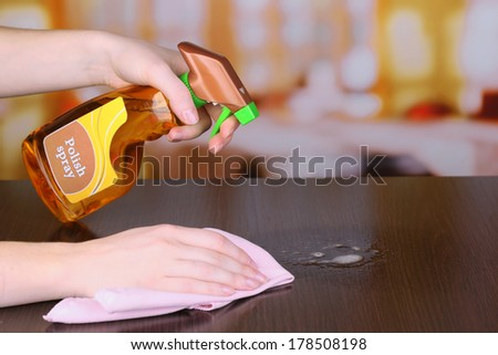 Hand cleaning wooden table with furniture polish - stock photo
