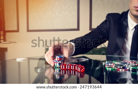 Hand close up. A man in a business suit sitting at the game table. Male player. Passion, cards, chips, alcohol, dice, gambling, casino - it is as male entertainment. Dangerous fun card game for money. - stock photo