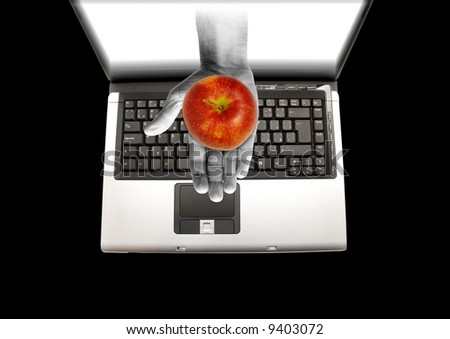 hand coming out of a laptop screen holding a red apple - stock photo