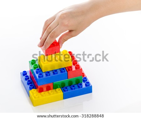Hand completing colorful plastic brick structure on white background - stock photo