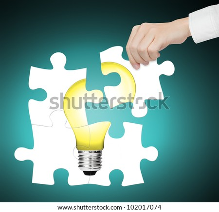 hand completing jigsaw puzzle of  light bulb, sign of idea, innovation, creative, smart, vision, solution, energy, electric etc. - stock photo